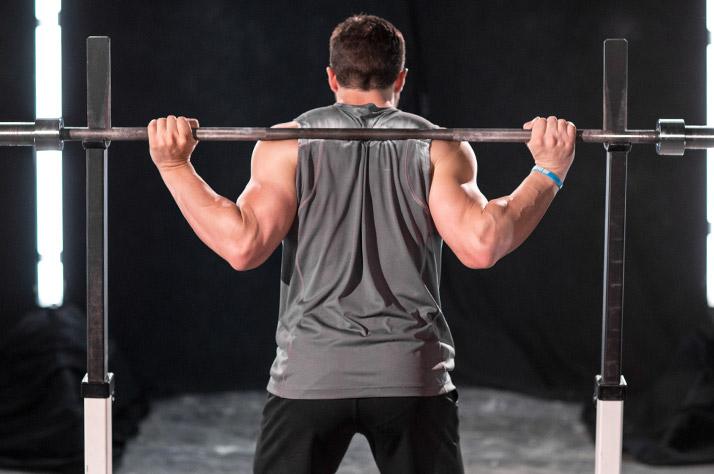 Как приседать со штангой: учебное руководство Лейна Нортона. В приседаниях с низким хватом штанга находится примерно на два дюйма ниже трапециевидных мышц и лежит на дельтовидных мышцах. Эта позиция не такая удобная, потому что плечи сведены